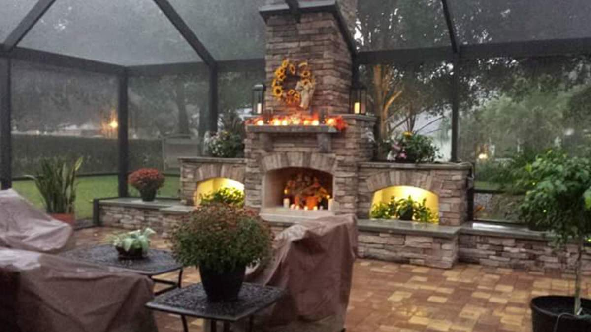 DIY fireplace built by a homeowner inside a framed in screen porch.
