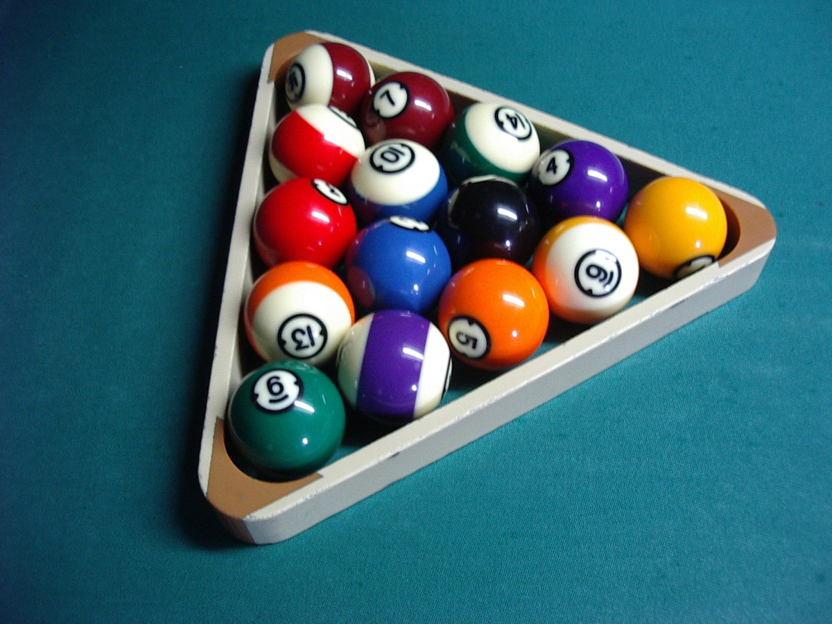 A view of the racked balls from the side.  The yellow ball is on the spot.  The black is centred.  The bottom corners show an alternate stripe and a solid colour. The balls are still loose within the rack