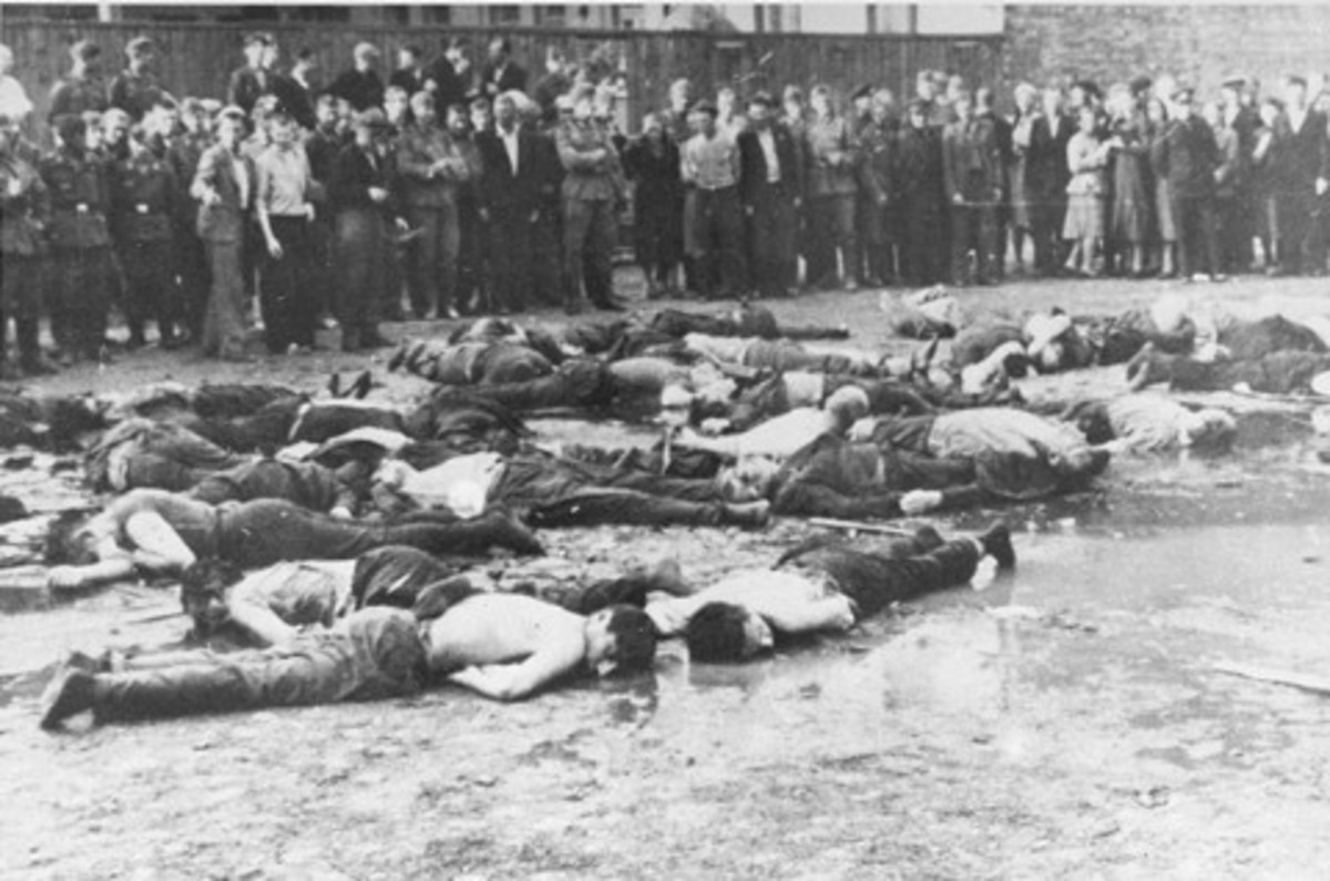 Crowd views the aftermath of a massacre at Lietukis Garage, where pro-German Lithuanian nationalists killed more than 50 Jewish men. The victims were beaten, hosed, and then murdered with iron bars. Kovno, Lithuania, June 27, 1941.