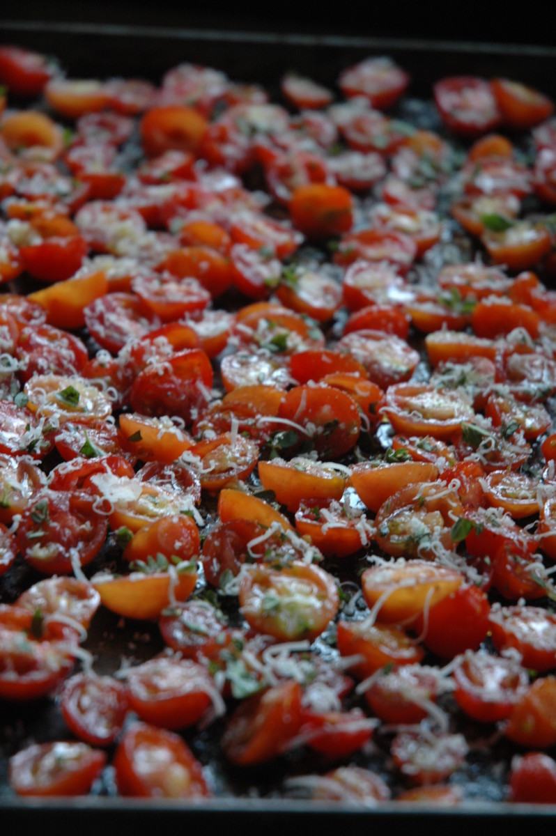 Cherry tomatoes, seasoned with fresh herbs and cheese, ready to roast to perfection.