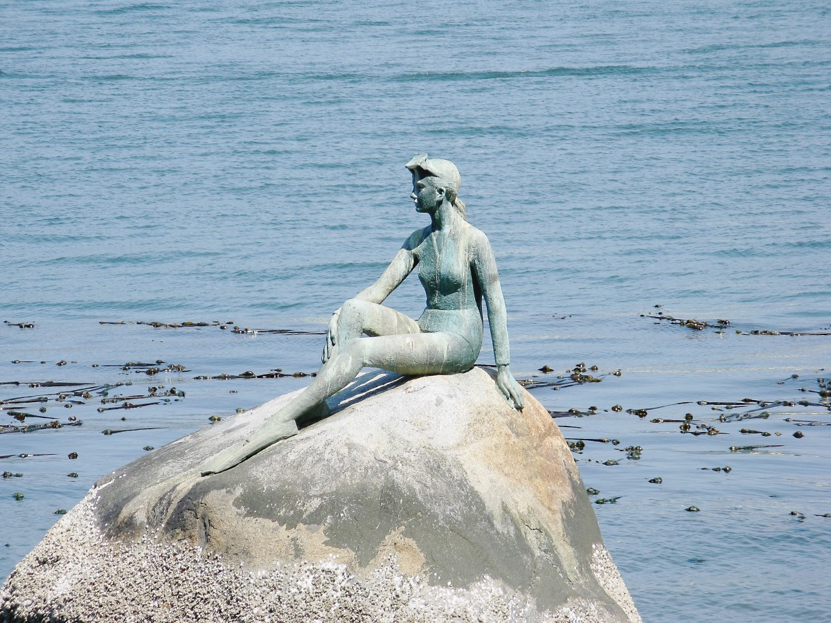 The Girl in a Wetsuit sculpture by Elek Imredy with bull kelp in the background