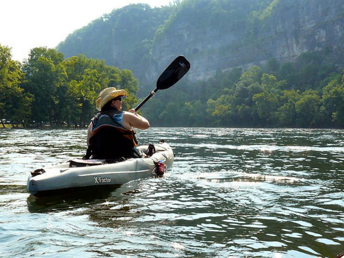 Woman paddling a kayak.