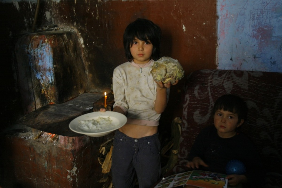 Small boy in poverty asking for food. Wearing dirty clothes as if he has not showered for several days.