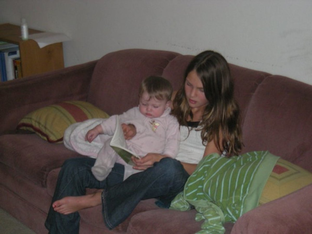 Big sister is reading to baby sister.