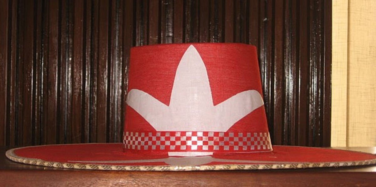 Eyo Laba Hat - A red hat with a white emblem and a chequered band, worn by the Eyo Laba masquerades.