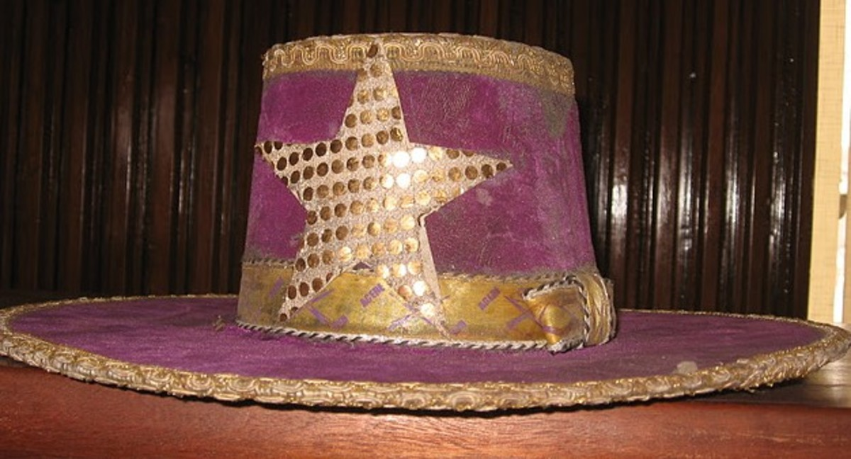 Eyo Agere Hat - The purple hat with a star emblem with gold dots, and a gold band is worn by the Eyo Agere masquerades.
