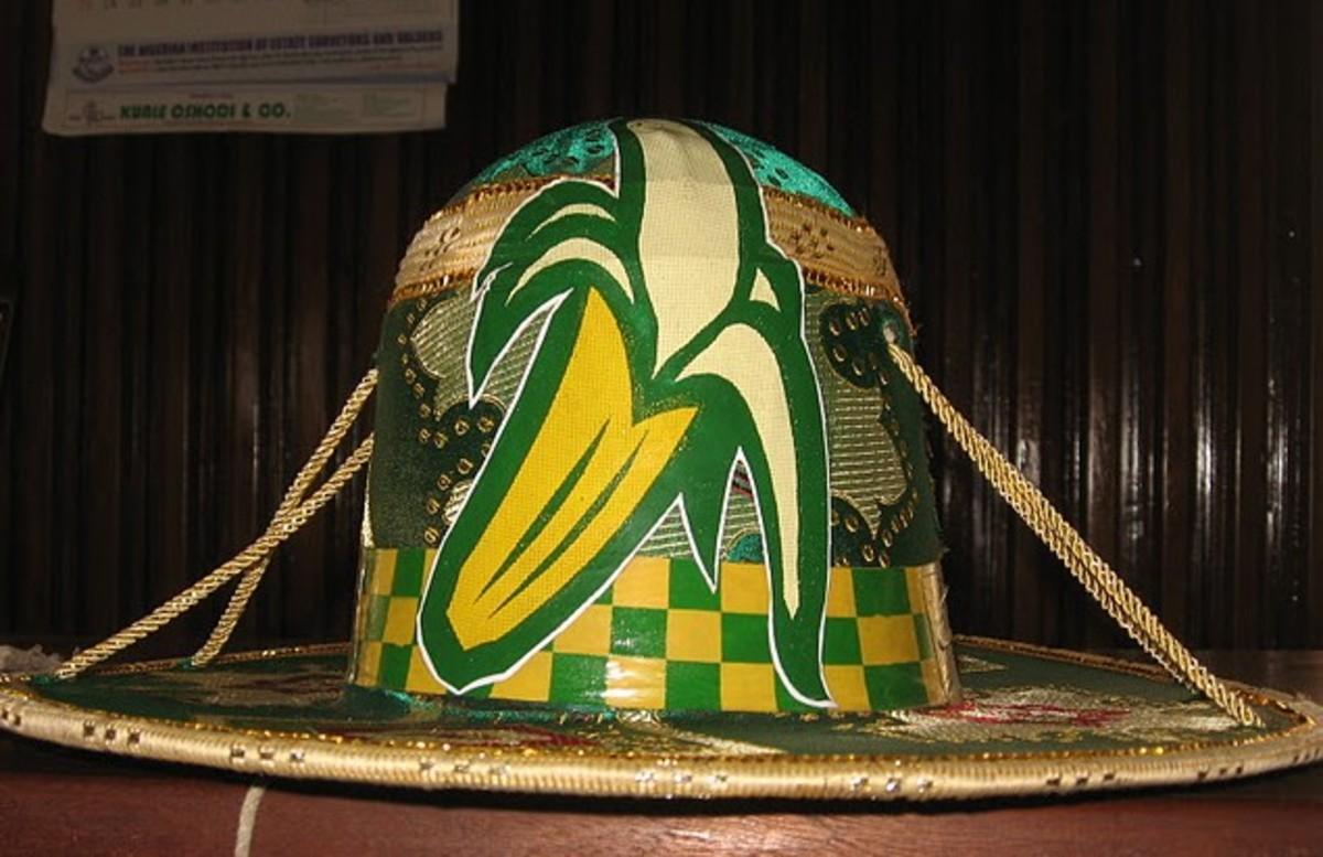 Eyo Ologede Hat - This group's very stylish hat has an elaborate emblem of a banana and a chequered green and yellow band. (Ogede is banana in Yoruba language)