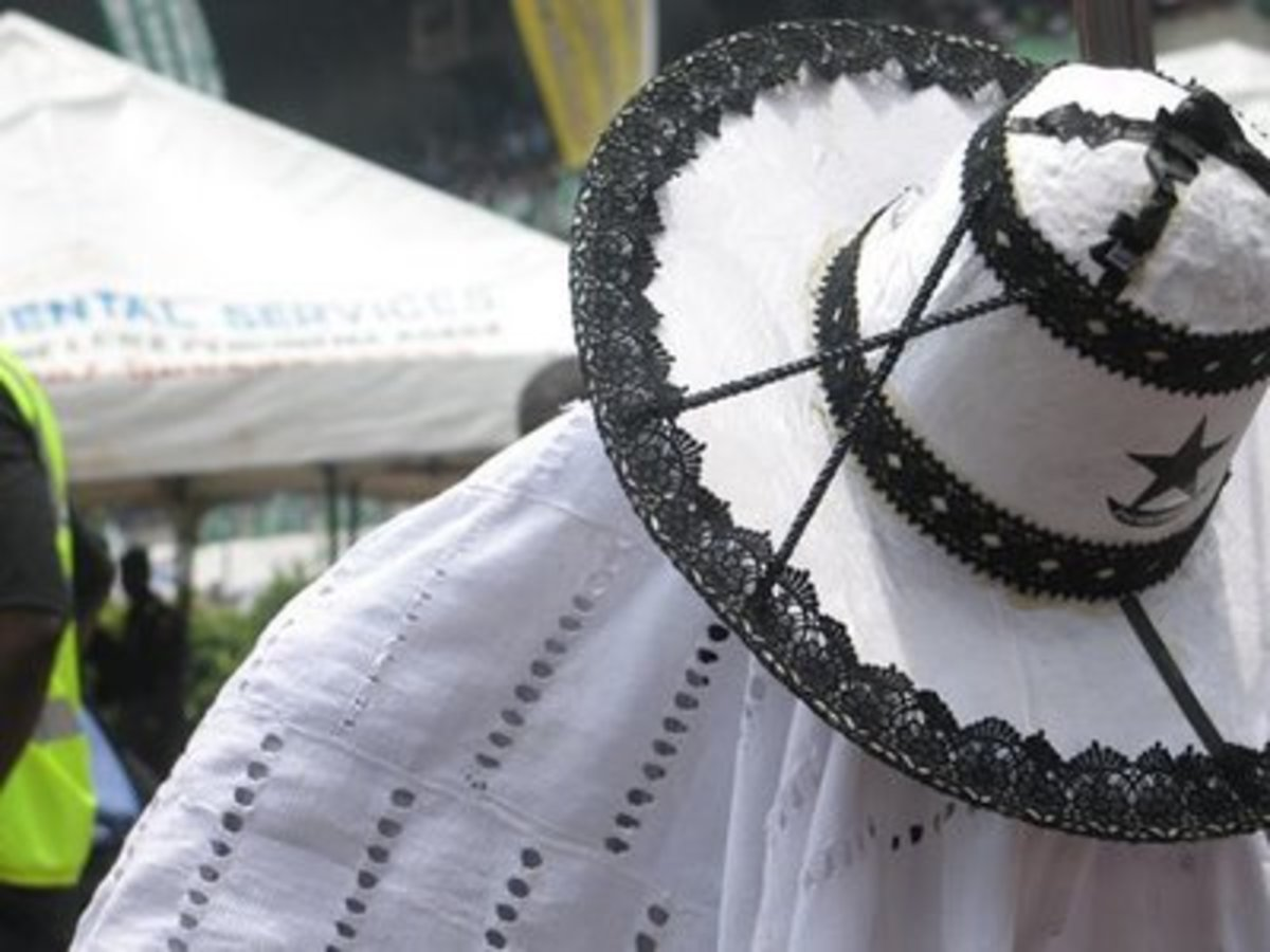 Adimu Orisa Hat - A predominantly white hat with black embroidery works. This style of hat is worn by the most senior Eyo masquerades.