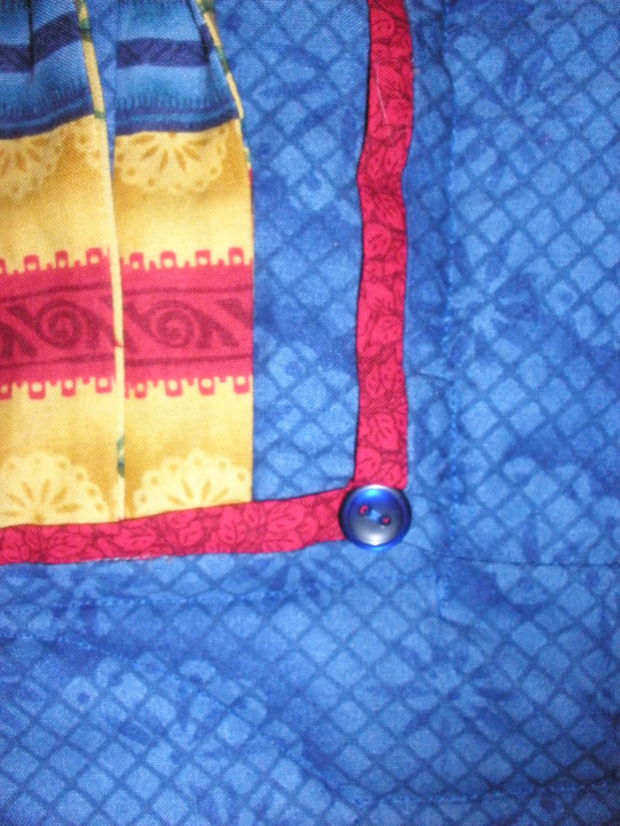 A button adds extra embellishment to the flange. Note that in addition to the red flange, the body of the quilt is made up of a series of flanges.