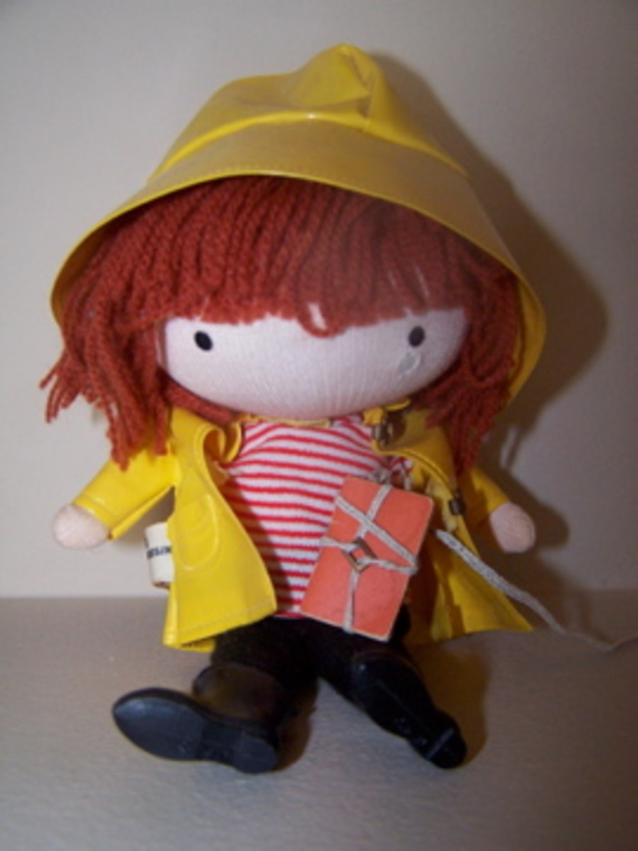 This Anglund Pocket Doll has its raincoat, rain hat, boots and book bag with string.