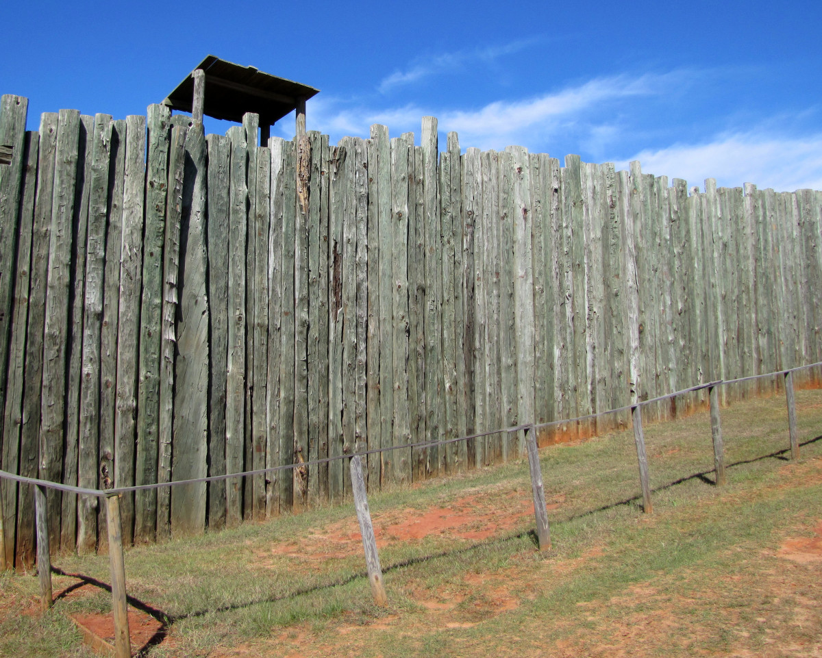 This shows what the stockade wall looked like with a guard tower. The reconstructed dead line is the short fence in the foreground.