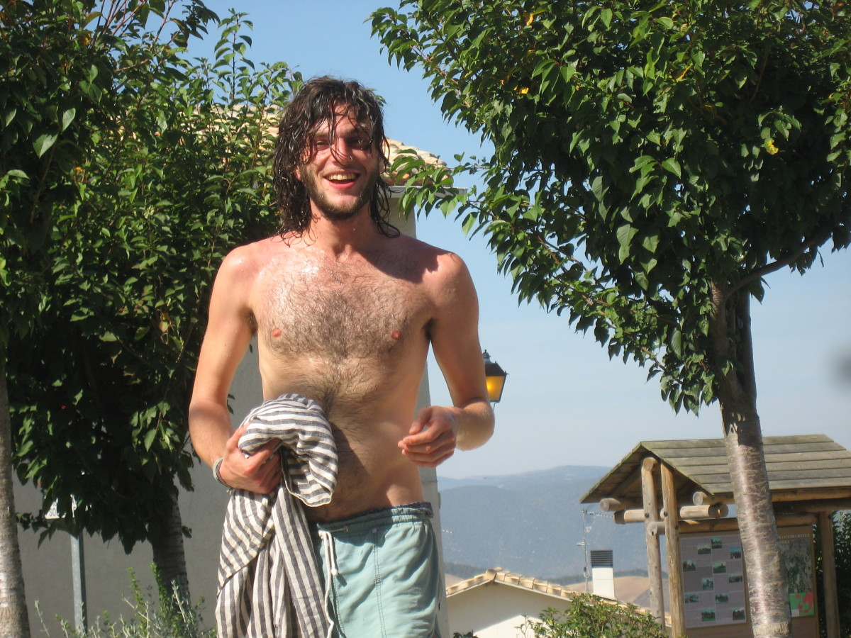 Noam happily washes at a public fountain on a very hot day.
