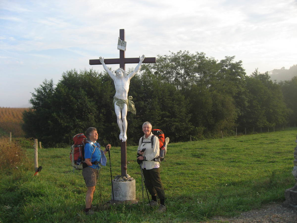 Marie-Belle and Linda stop by a statue of Jesus who protects the way.
