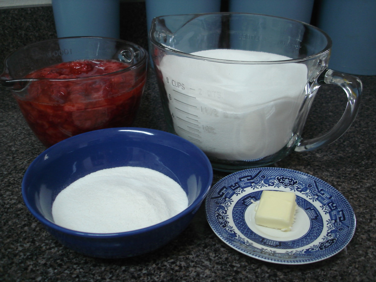 All the ingredients needed for jam: strawberries, sugar, pectin, and butter.