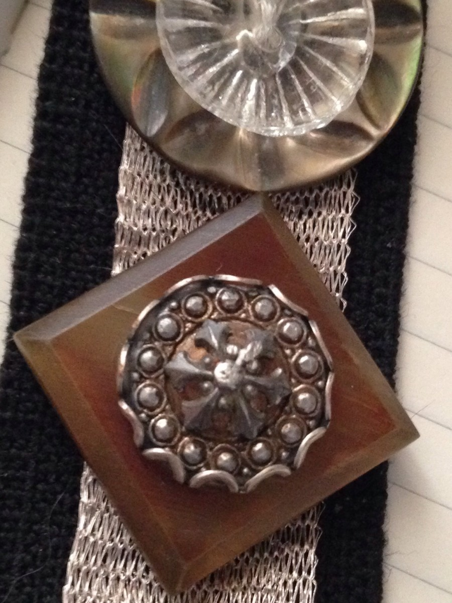 A Victorian metal button stacked on top of a celluloid coat button creates a dramatic statement.