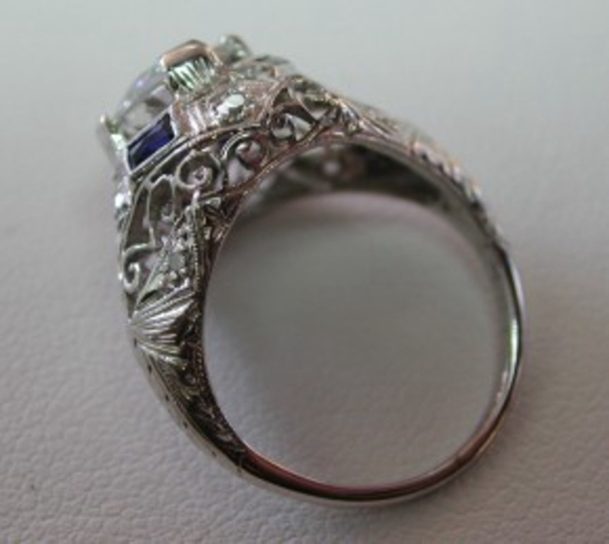 A genuine antique platinum ring with filigree, calibrated-cut sapphires and accent diamonds.