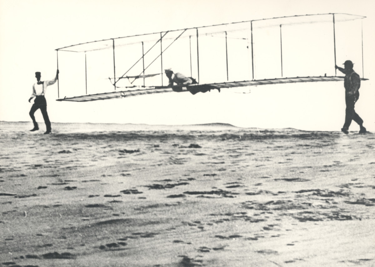 Historic photo of the Wright brothers' third test glider being launched at Kill Devil Hills, North Carolina, on October 10, 1902. Wilbur Wright is at the controls, Orville Wright is at left, and Dan Tate (a local resident and friend of the Wright bro