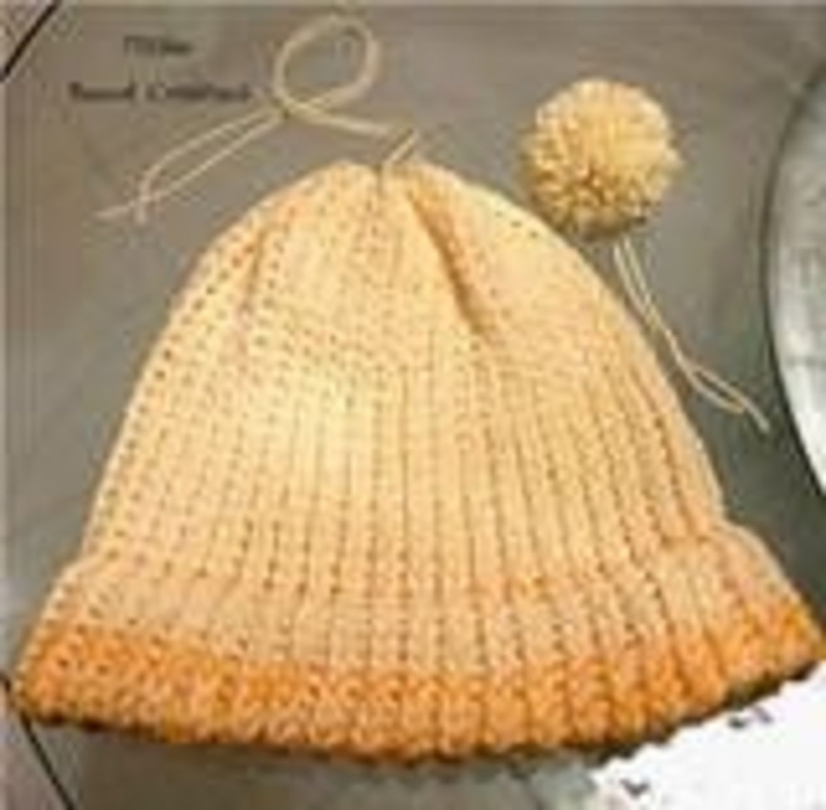 Finished Knit Hats and  Pom Poms have Two (2) Leftover Strings that you can use to attach them together.