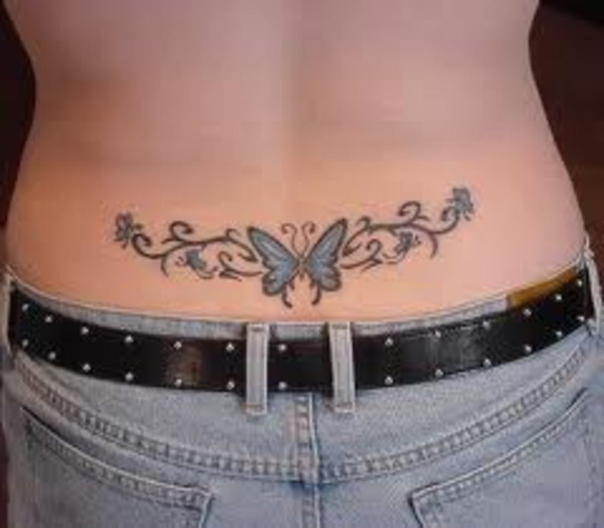 Beautiful art surrounds this butterfly lower back tattoo