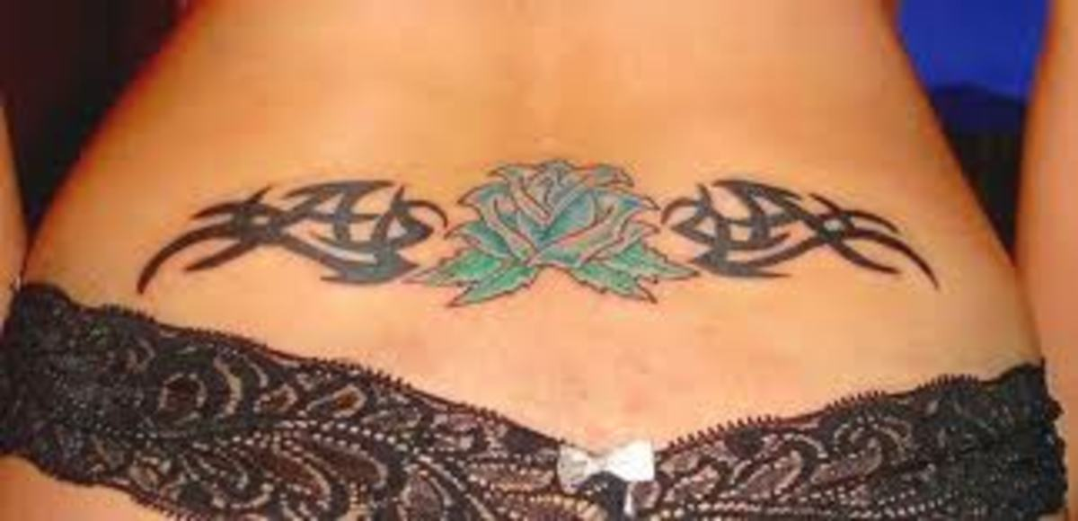 Lower back lotus tattoo with tribal art