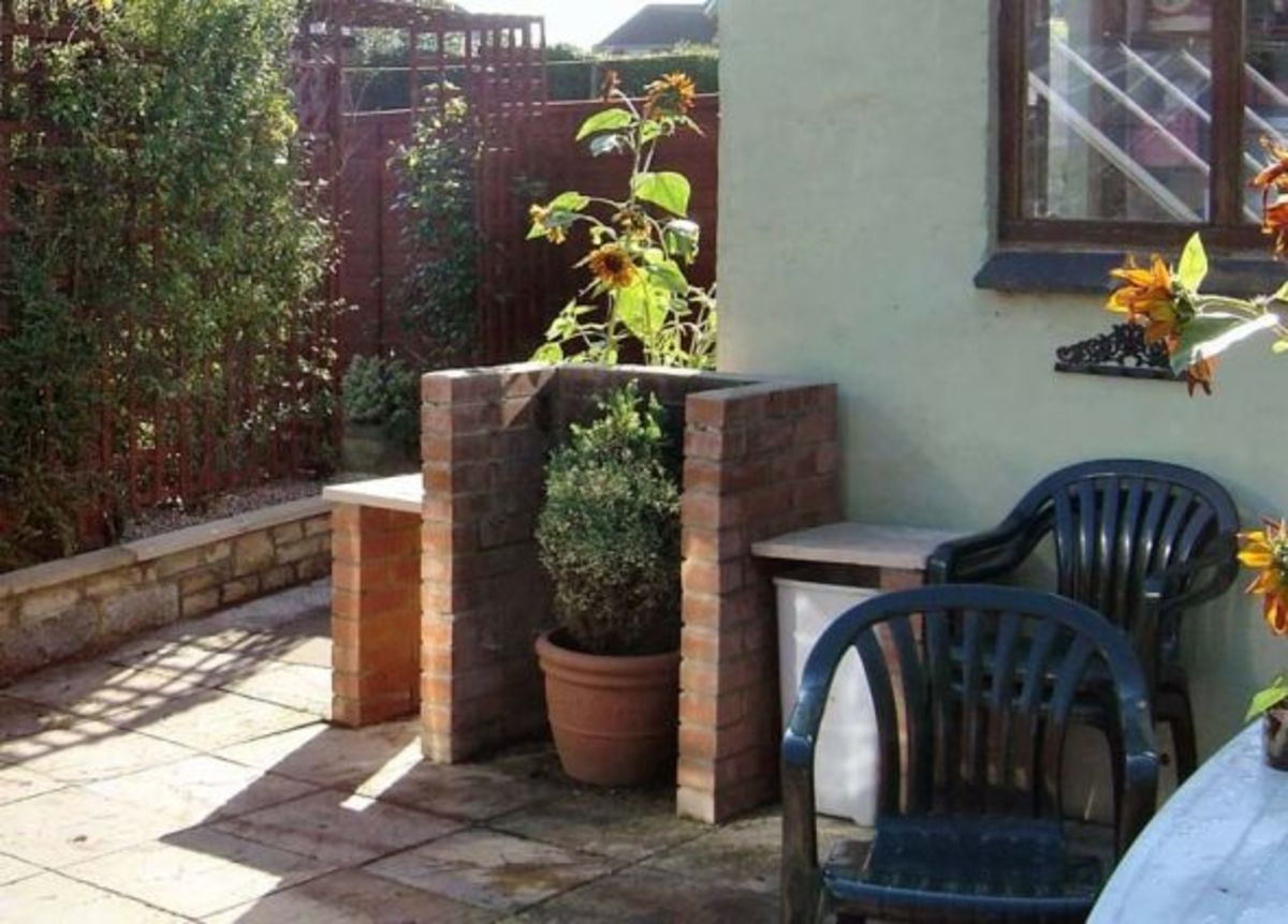 Brick BBQ used for potted plants when not in use.