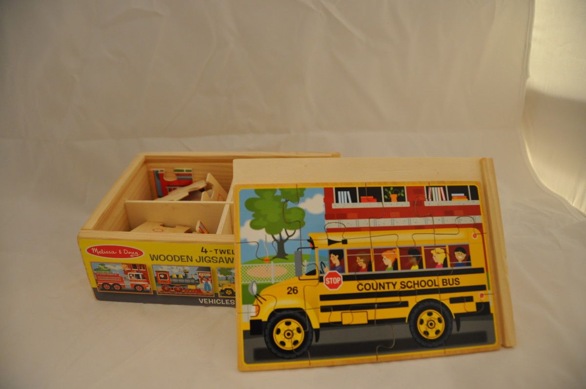 Boxed set of four 9-piece puzzles. No pictures of puzzles except small illustrations on side of storage box.