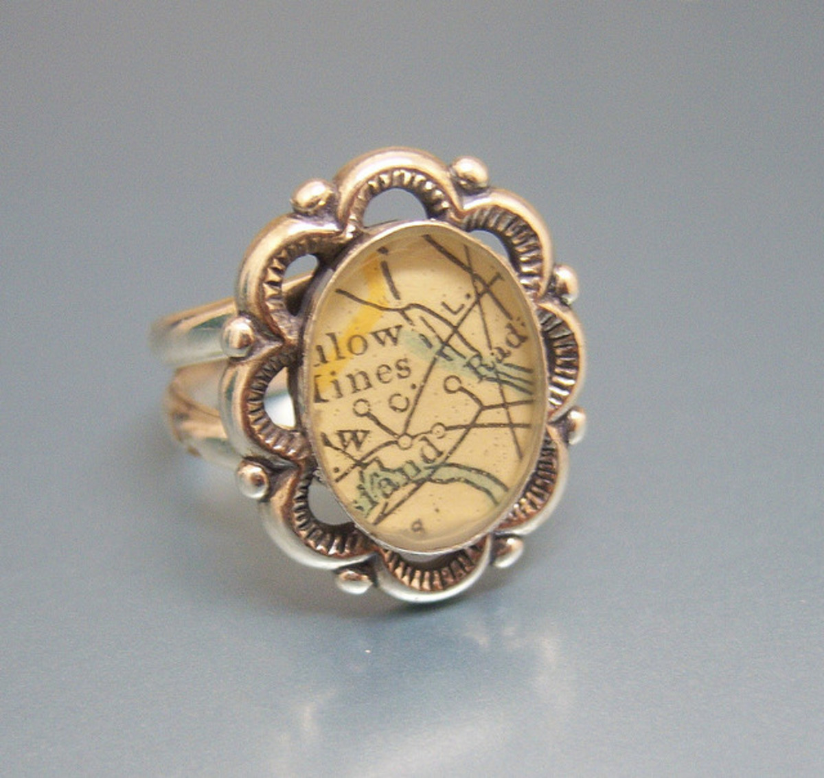 A vintage inspired ring with a scrapbook image of an old fashioned map