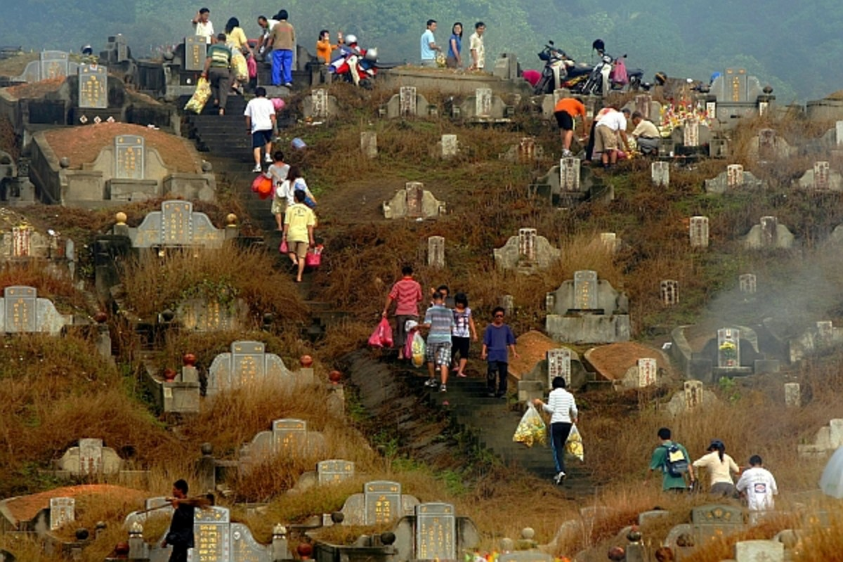 Typical scene during Qing Ming festival with family members bringing offerings for prayer, cleaning & tending to the graves