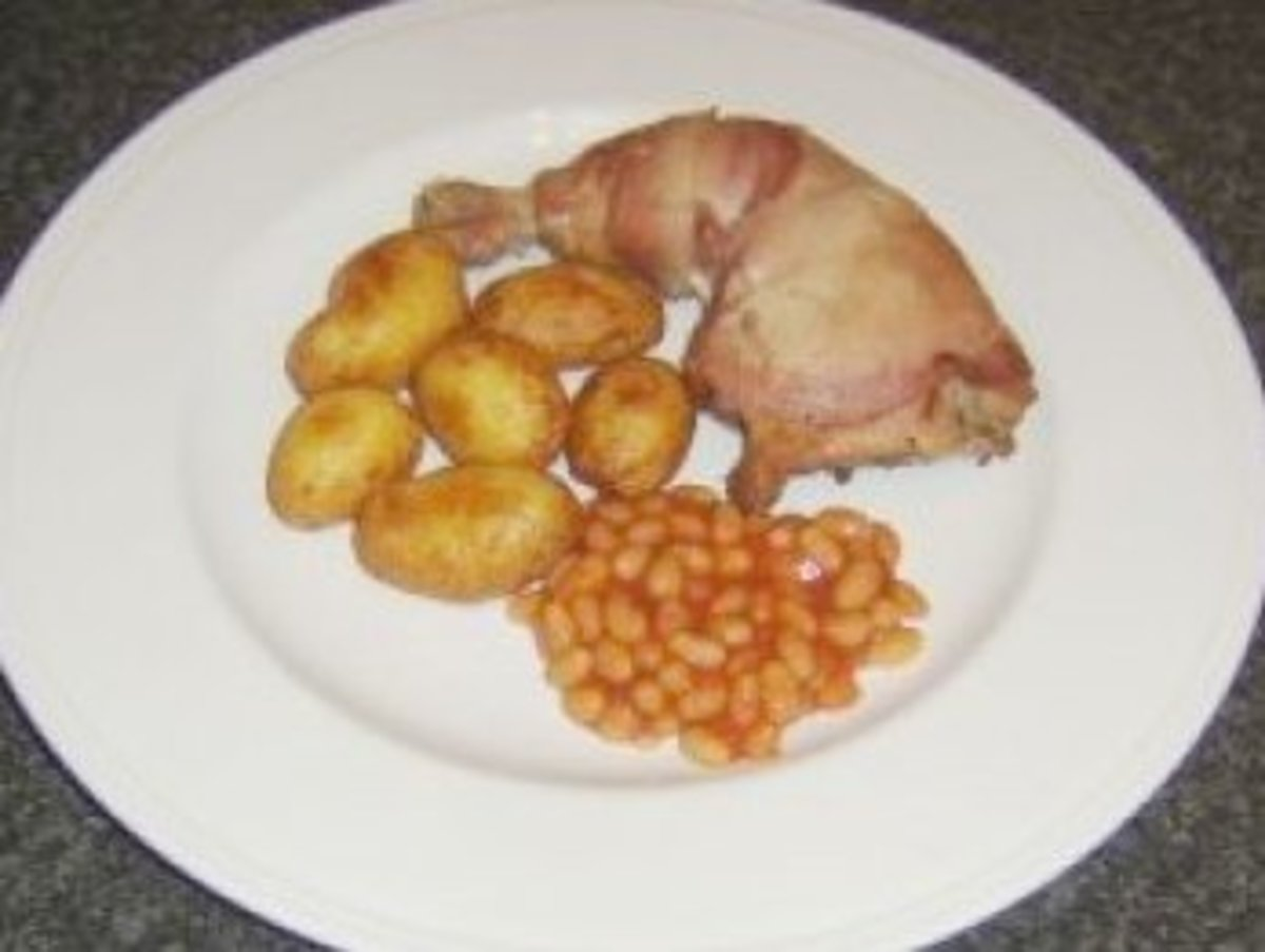 Whole roast chicken leg in bacon with roast potatoes and beans