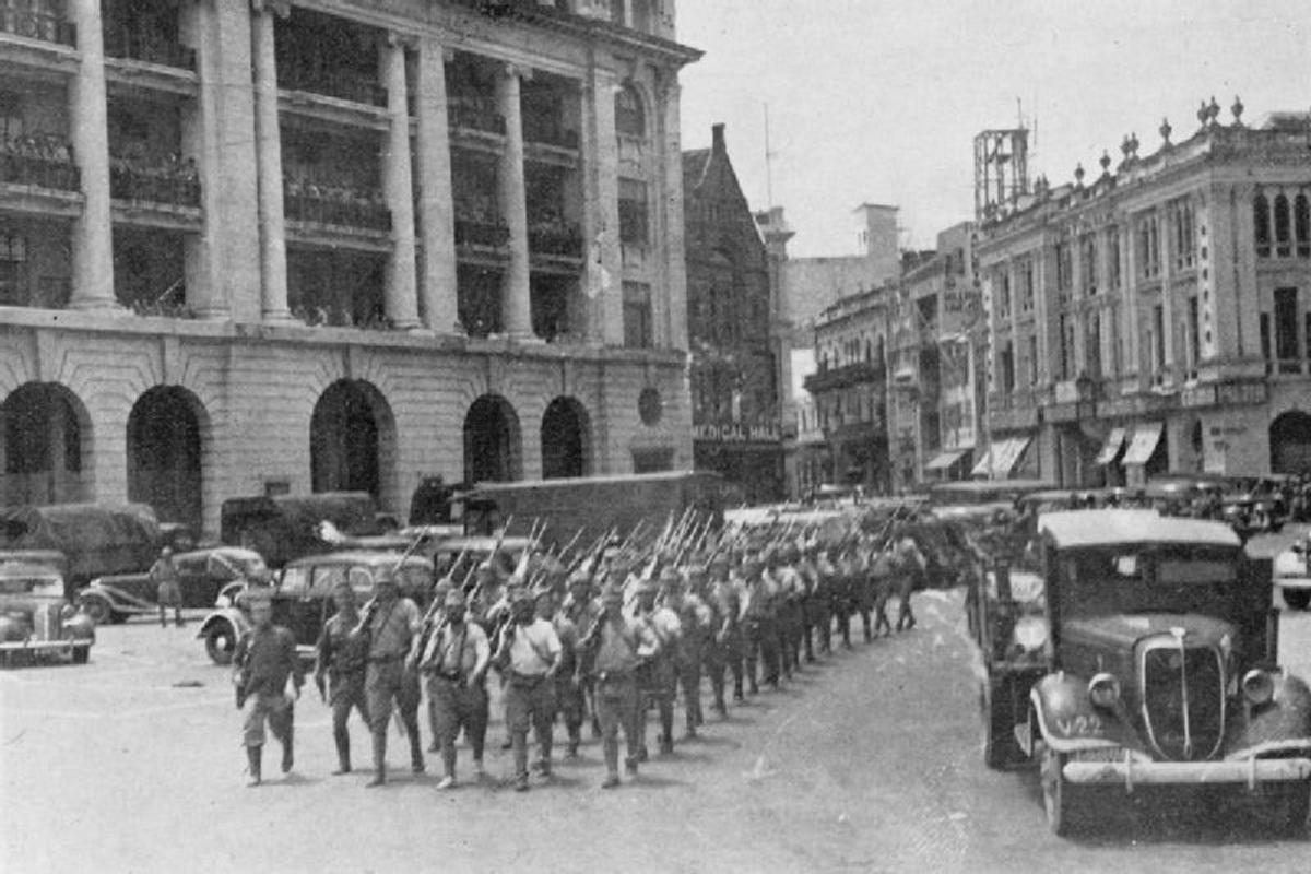 The Japanese marching victoriously through Fullerton Square in Singapore City.
