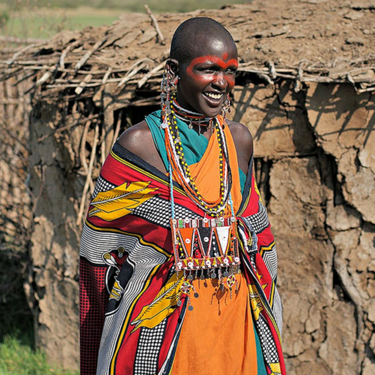 A painted Maasai woman near a Maasai Manyatta (Hut) built from dried cattle dung.
