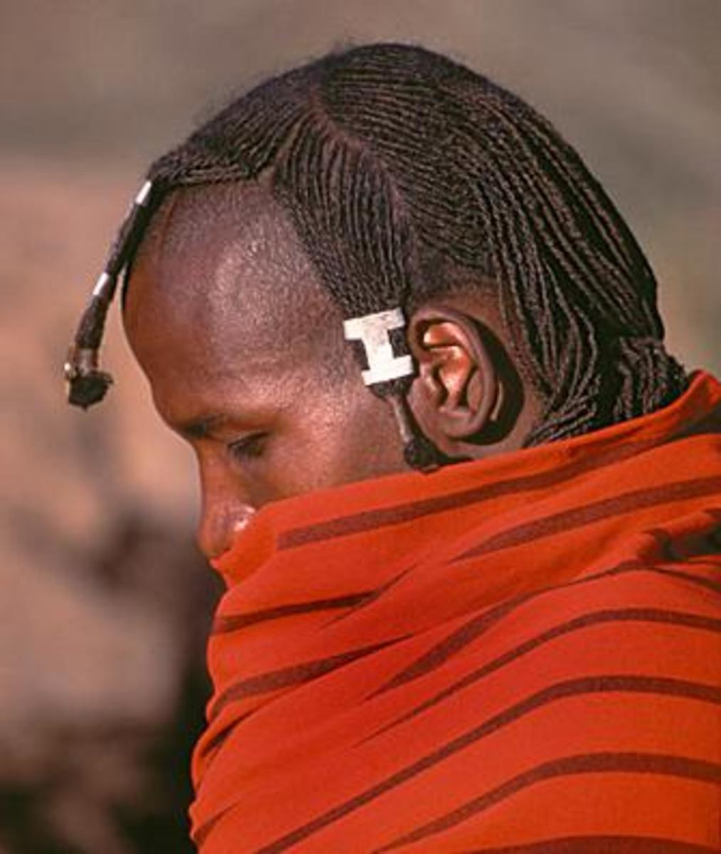 After circumcision, the young warriors grow their hair again and spend a great deal of time styling it. The plaited hair is dressed with animal fat and ocher, and parted across the top of the head at ear level.