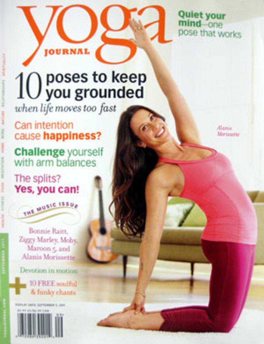 Alanis Morissette on cover of Yoga Journal doing the camal pose.