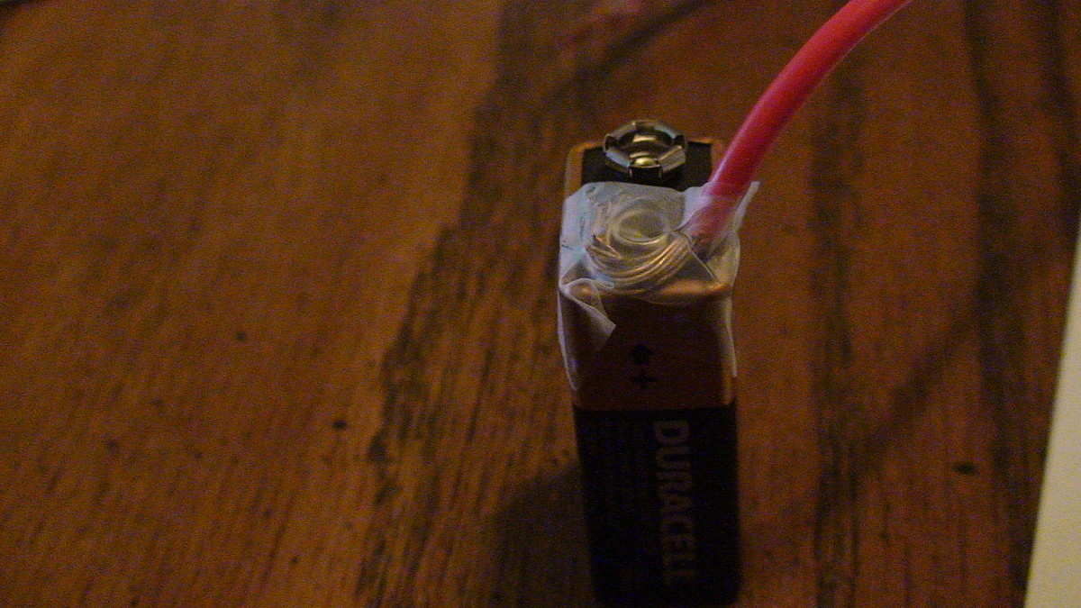 Attach the stripped end of one copper wire to the positive end of the battery.
