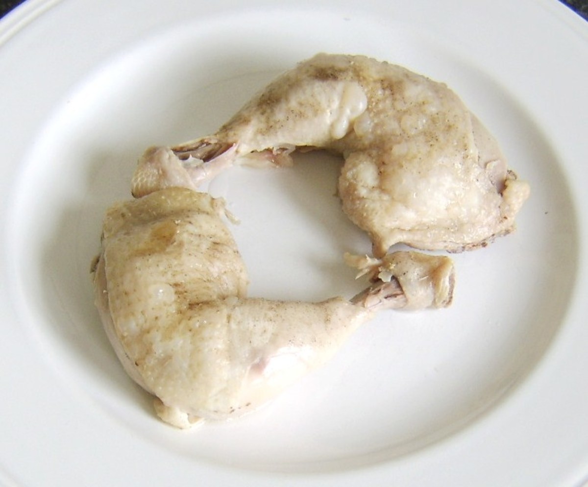 Cooked chicken legs are removed from pot with slotted spoon