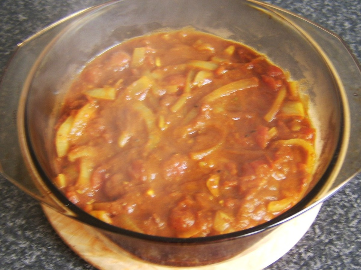 Bhuna sauce is poured over chicken legs in casserole dish
