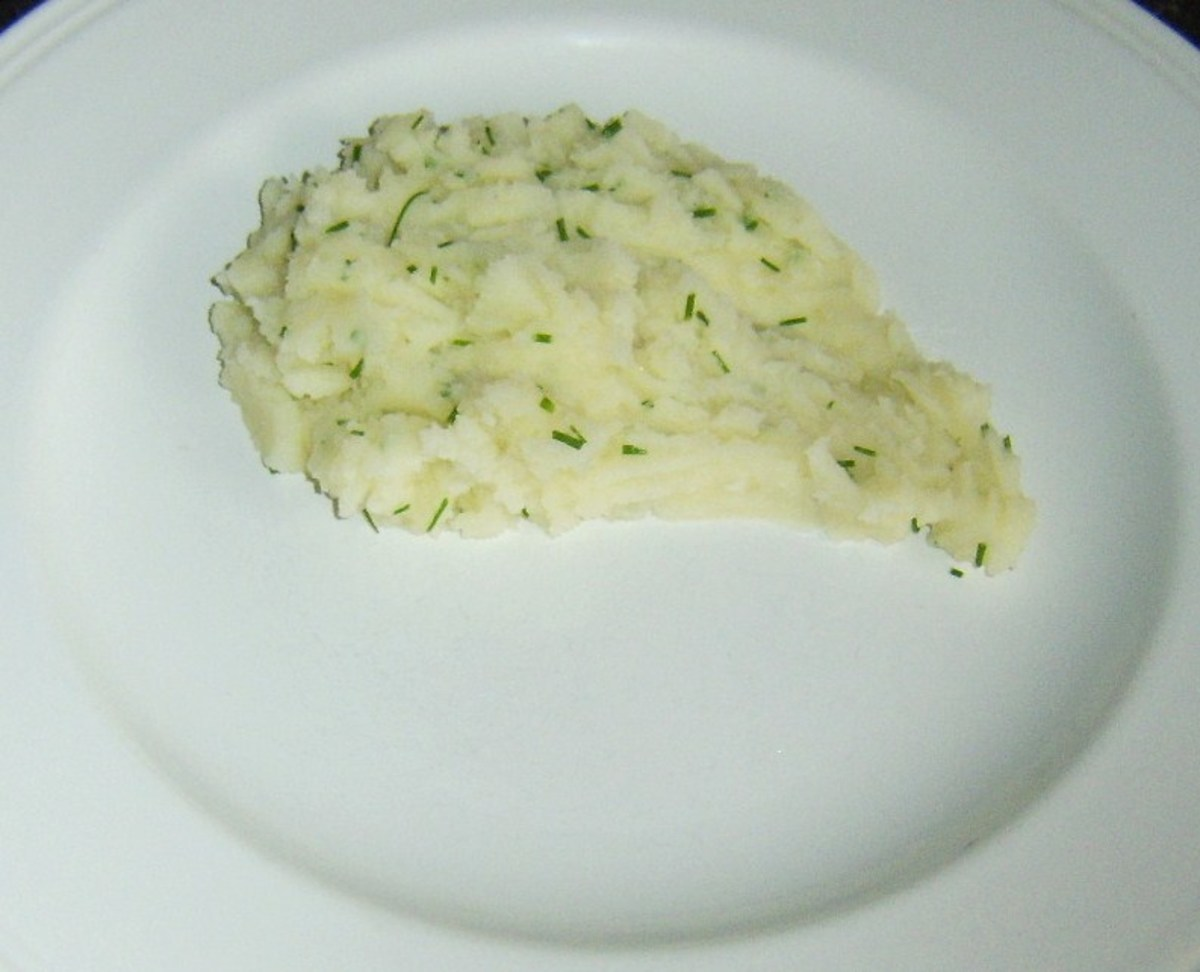 Mashed potato is plated in a shape ready to accommodate the chicken leg