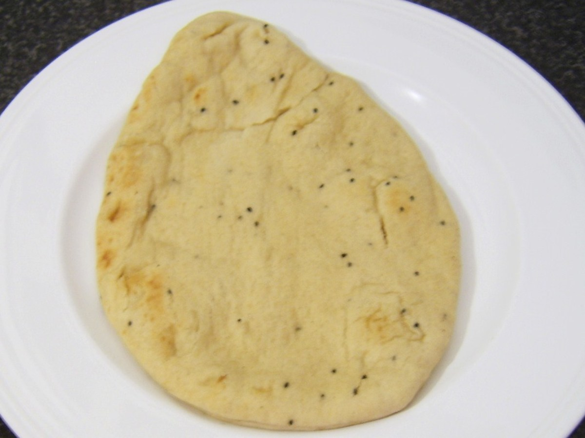 Naan bread is served with chicken leg bhuna
