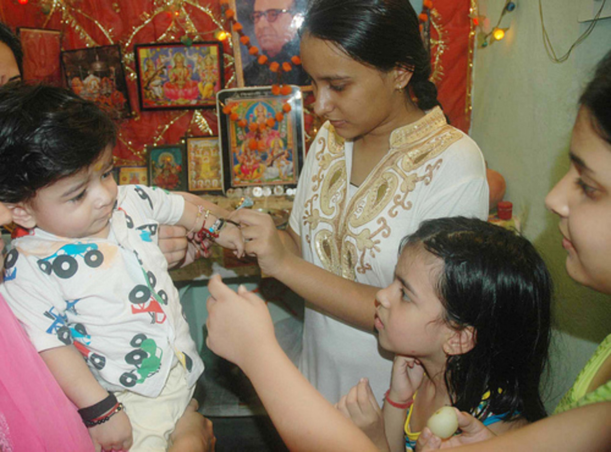 sisters tying rakhi on their younger brother's wrist