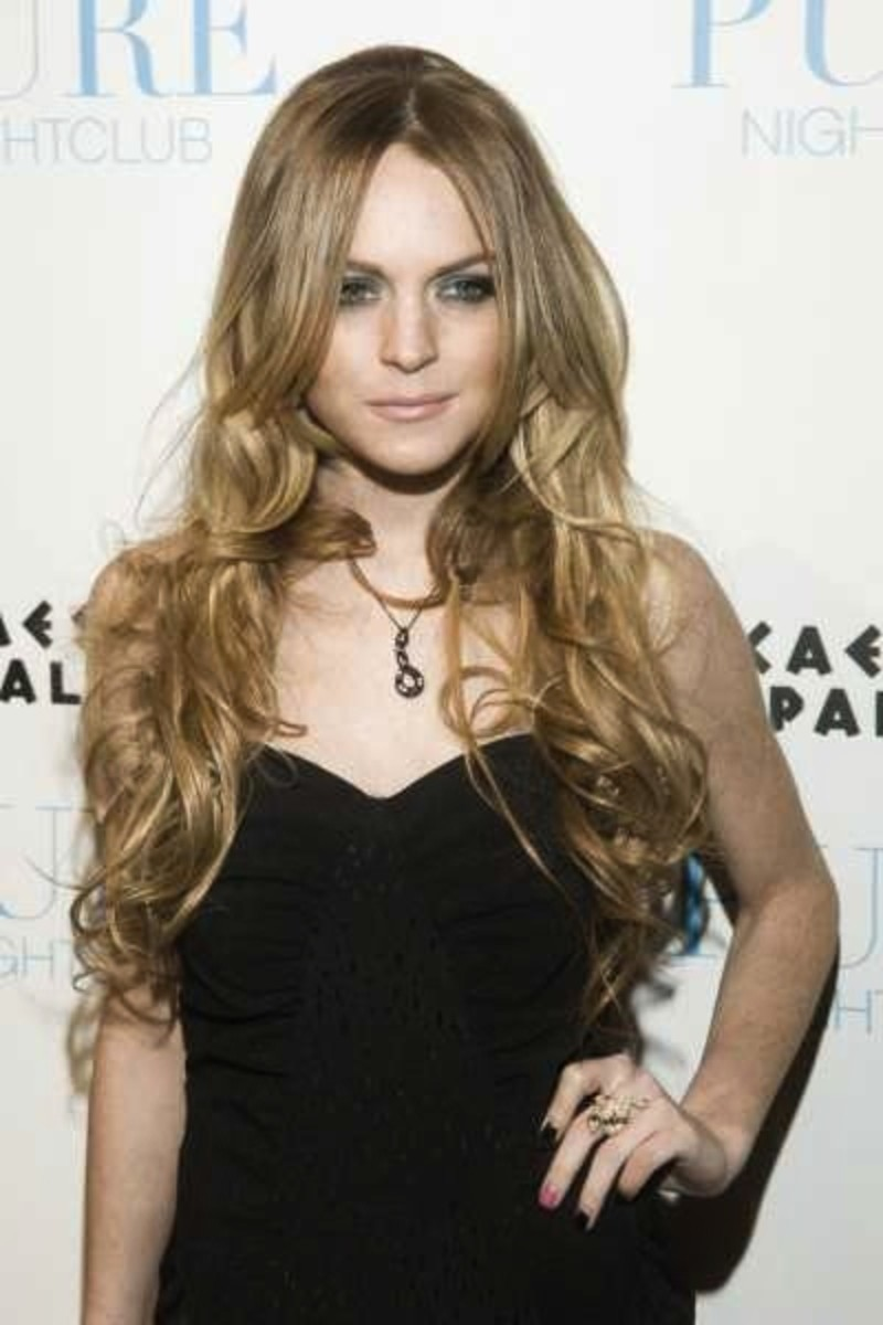 Lindsay Lohan with medium ash blonde hair, very long and curly.