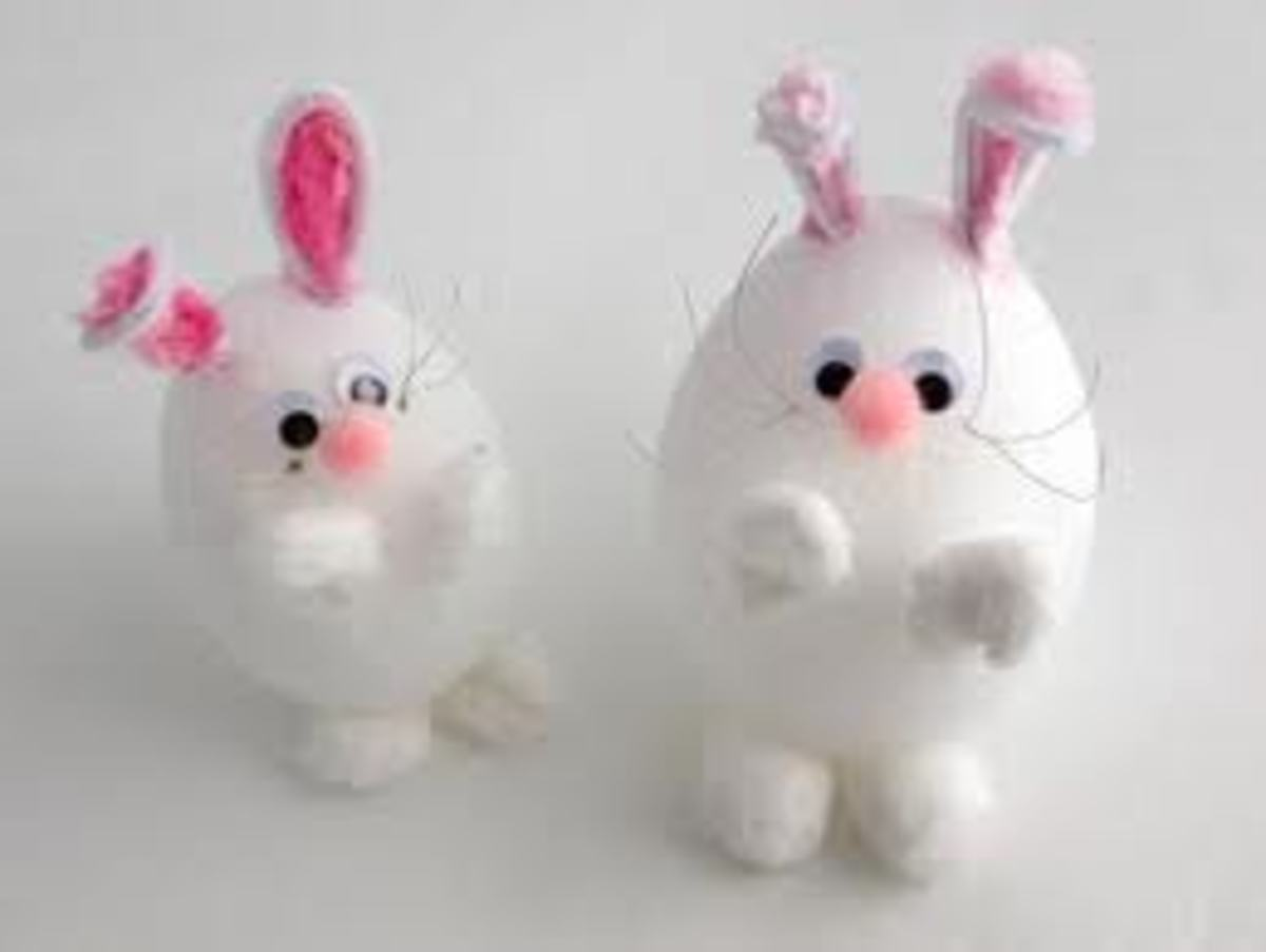 CUTE BUNNIES MADE WITH EGG-SHAPED FOAM BODIES, WHITE POM-POMS, A PINK POM-POM NOSE, GOOGLE EYES, AND WHITE AND PINK FOLDED PIPE-CLEANER EARS
