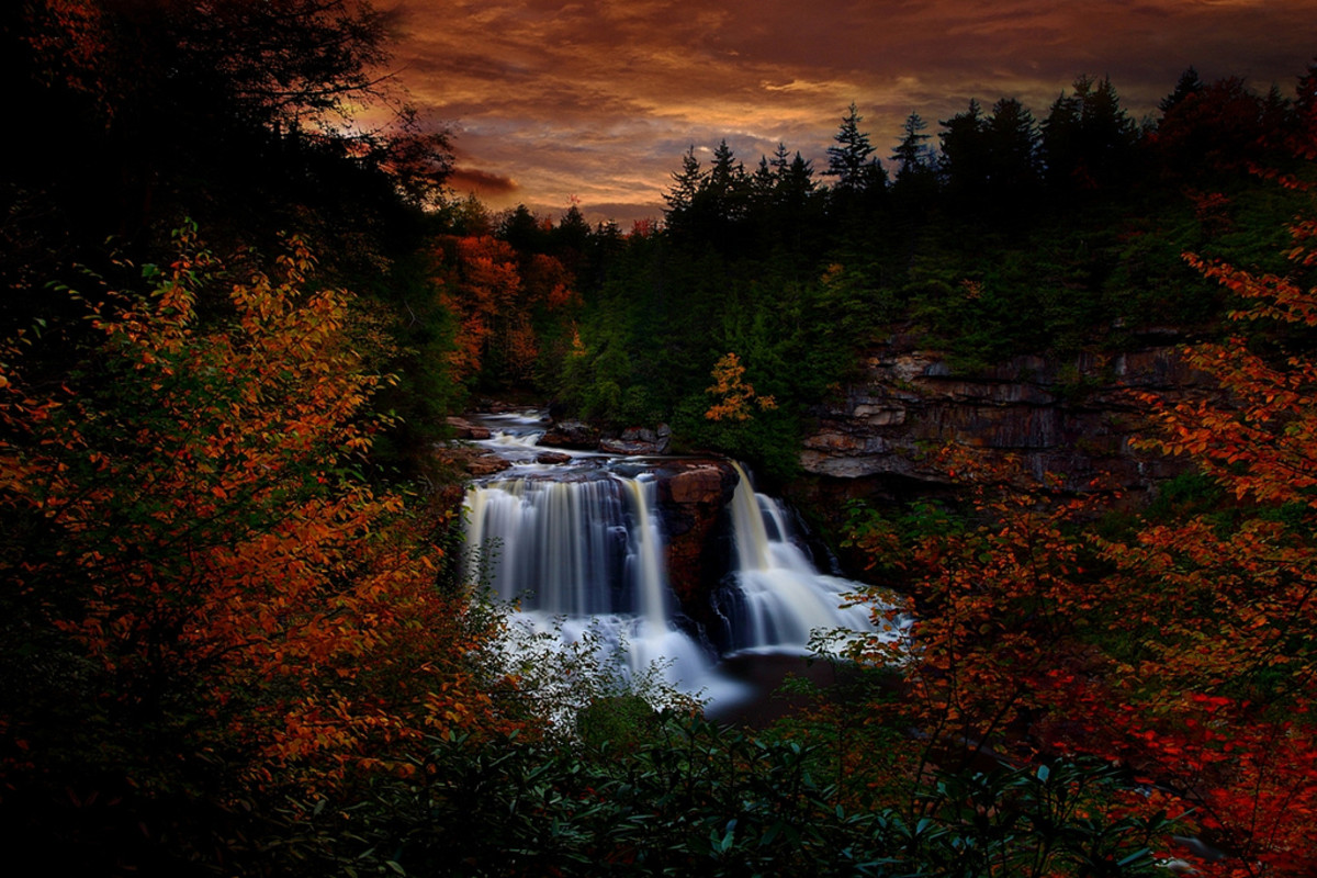 A slow shutter speed (and a tripod) is used to capture a waterfall at sunset, surrounded by fantastic fall foliage.
