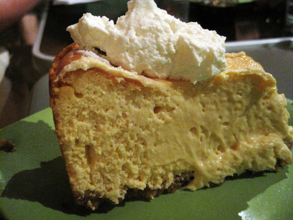 A scoop of fresh whipped cream completes a piece of pumpkin pie.