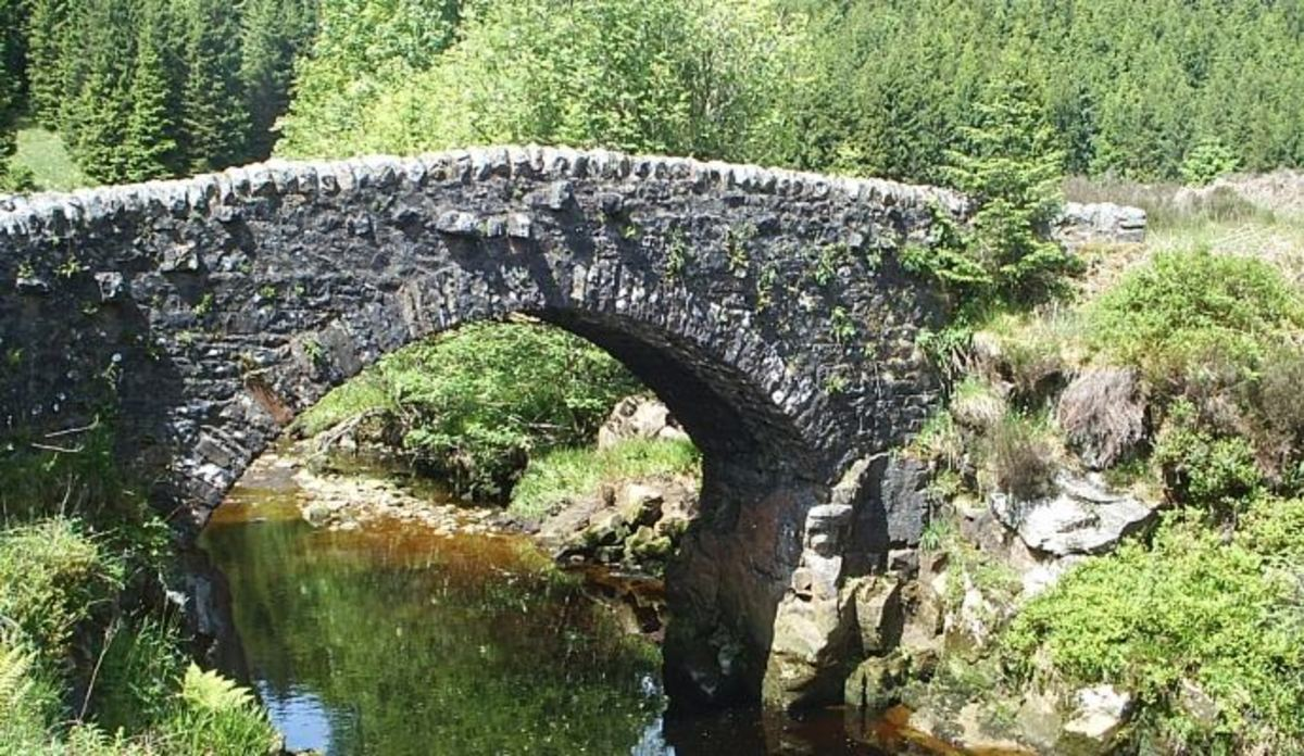 Above Kielder WAter, an old stone bridge nestles between the banks of the burn - It was the Angles who taught the Scots their English. Many Northumbrian dialect words stem from this time