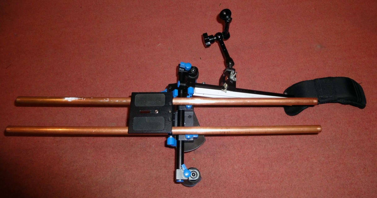 Shoulder Rig adjusted for left shoulder with camera plate on top, hand grips below and articulating arm and support clamp on the right.