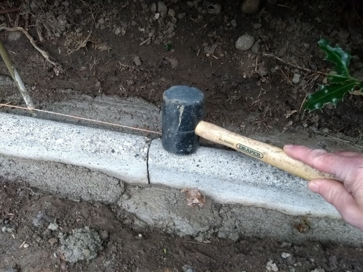 Use a mallet or the handle of a lump hammer to tap stones down into the bed. Don't use the hammer head itself to avoid chipping or cracking concrete. (Sorry this photo is out of sequence taken after haunching added at the front!)