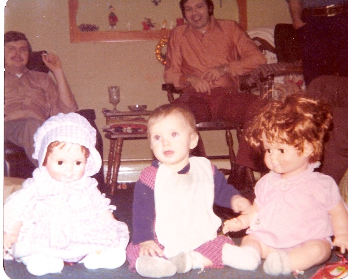 Seven months old posing with his sisters' dolls.