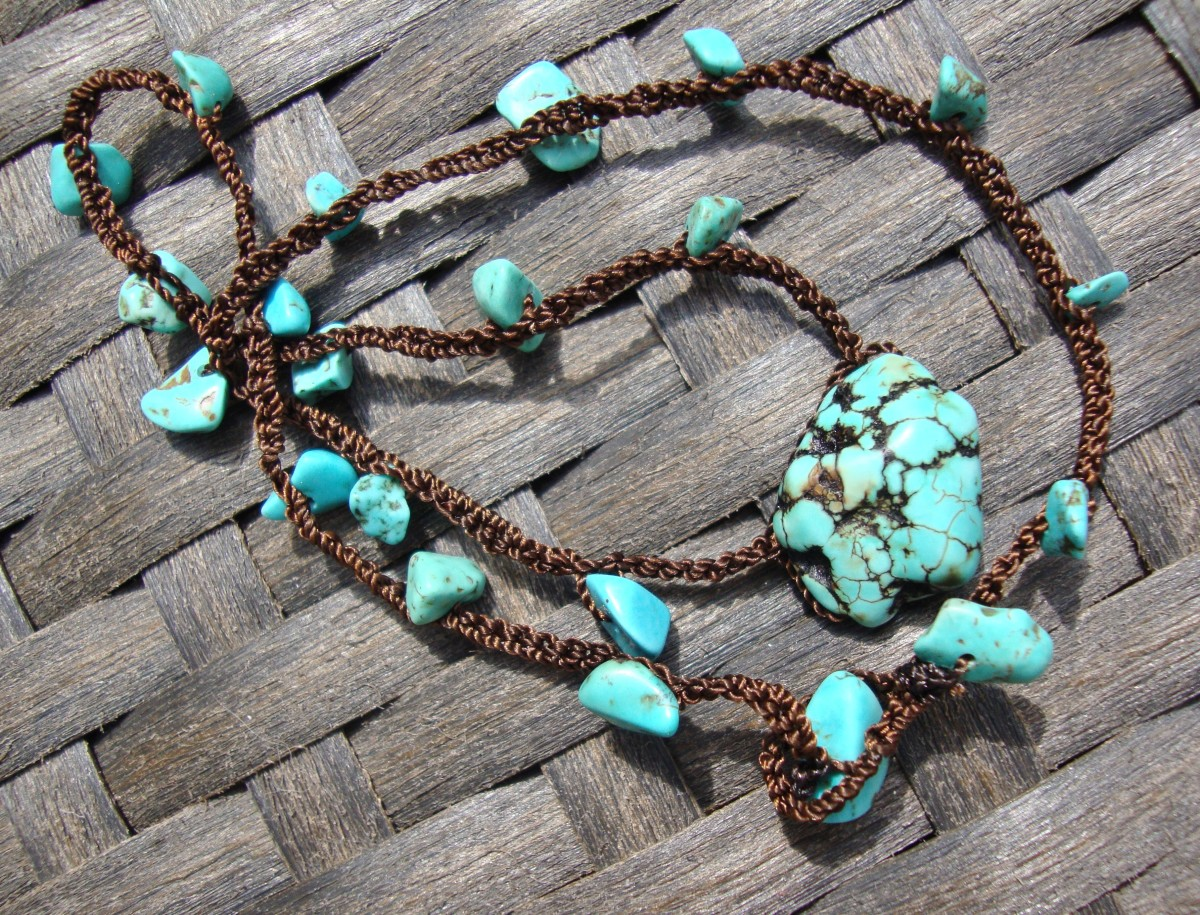 This is a tightly chained crocheted neclace with brown cording and turquoise nuggets.  The clasp is a loop and a larger nugget goes into it.