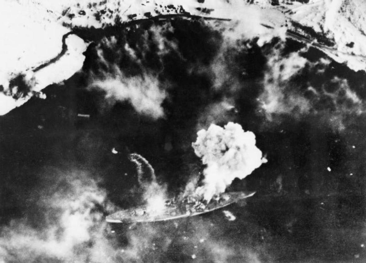 The Tirpitz under attack by the Fleet Air Arm bombers. There is a small speed launch rushing to get away and leaving a visible wake, on the left of the battleship, in the center of the picture- This action was in April 1944