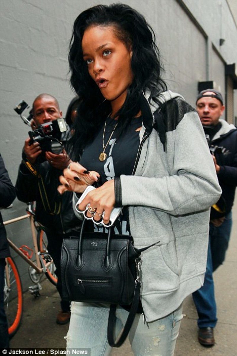 Rihanna is photographed by paparazzi holding her iPhone in one of the knuckle cases